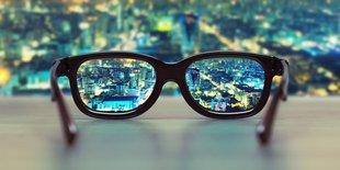 Brille mit klarer Sicht auf beleuchtete Stadt. Der Hintergrund ist dafür unscharf.