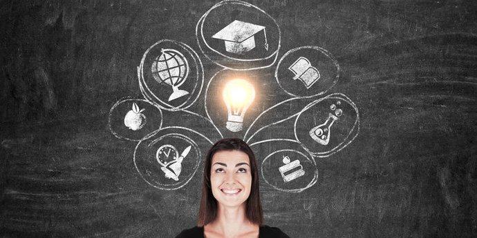 Frau vor Tafel mit skizzierten Wissenssymbolen